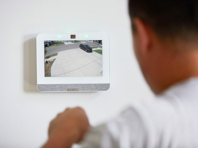 a man looking at the qolsys iq panel 4 as someone drives off the driveway at home for security
